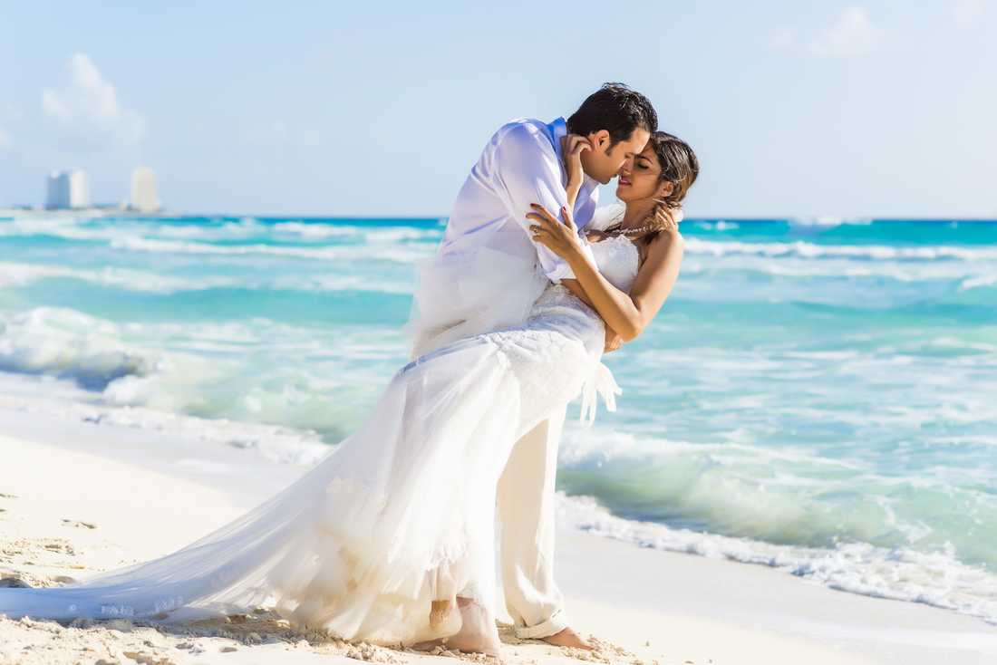 Bride and groom embracing each other on the beach