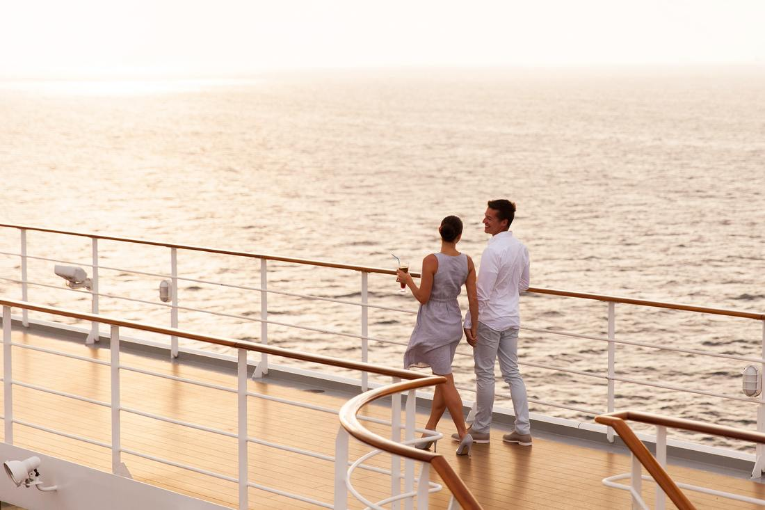 Couple holding hands on cruise ship deck at sunset